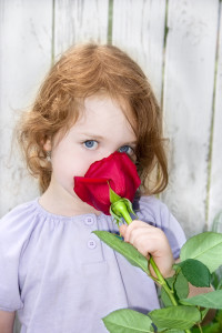 image of child smelling a rose